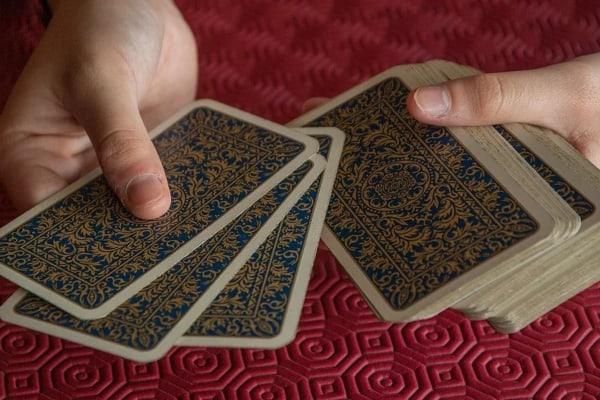 personas echando las cartas sobre tapete rojo